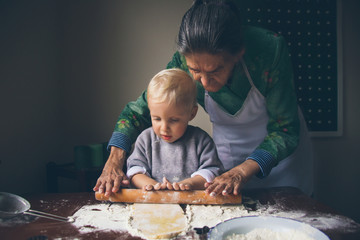 Little baker with grandmother knead Christmas cookies