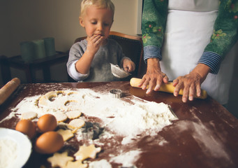 Little boy with grandmother preparing and eating Christmas cooie
