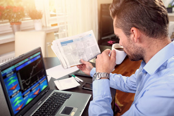 young businessman checks the stock price at home