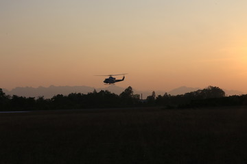 silhouette helicopter over airfield on sunset