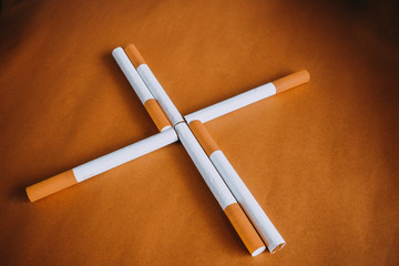 Some cigarettes with filter on brown background