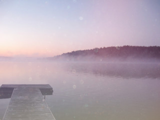 abstract photo of misty and foggy lake at morning sunrise.