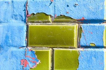 Blue and red paint peeling off green ceramic wall tiles
