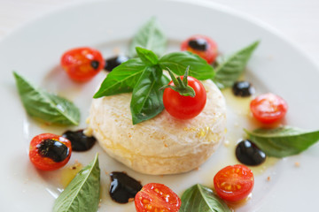 round piece of cheese with basil and cherry tomatoes on a white plate