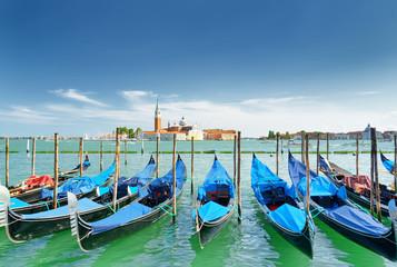 A row of gondolas parked beside the Riva degli Schiavoni. Venice