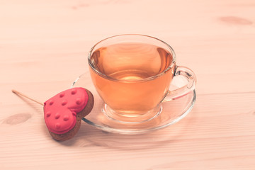 delicious fresh cookies in the shape of a heart on a white plate on wooden background. A Cup of green tea.Breakfast