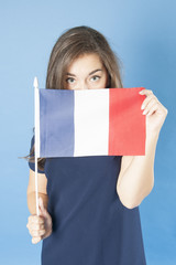Young girl looks out of the French flag..