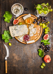 Gorgonzola Camembert on a wooden cutting board with a knife for cheese with honey and jam light grape on dark wooden background close up