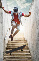 Professional skateboarder boy jumps off the stairs