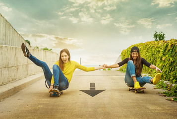 Skateboarder girlfriends roll down the slope