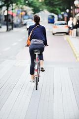 Woman on bike in green summer city