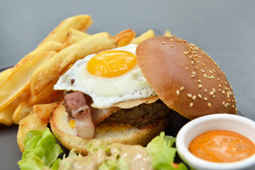 Lunch with burger, chips, eggs, sauce and salad on gray plate from stone slate