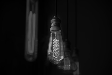 Hanged  decoration light bulbs in dark room focused on middle on