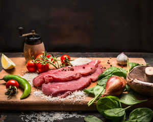 ingredients for cooking turkey steak on a wooden cutting board on a dark wooden background close up