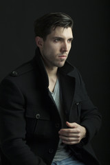 young attractive man in a coat  on black background
