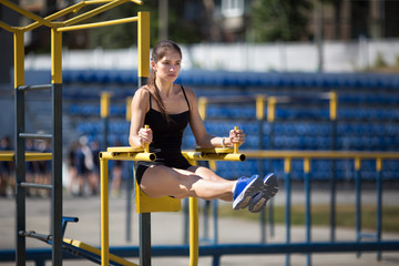 Beautiful young caucasian woman in fitness wear doing belly press exercises in a park at the morning