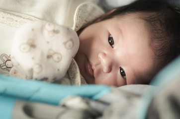 Portrait of cute asian baby looking on bed