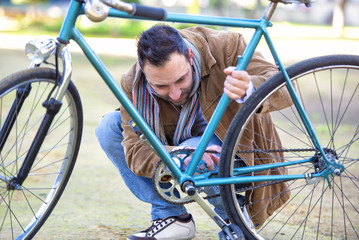 Man checking the chain an antique bicycle