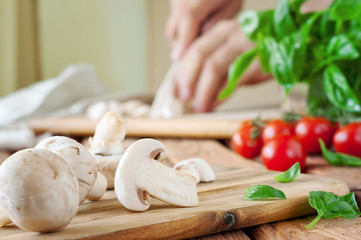 Sliced white button mushrooms on a cutting board with basil