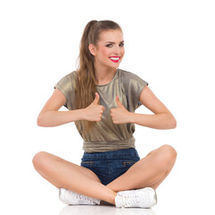 Smiling young woman sitting on a floor with legs crossed and showing thumbs up. Full length studio shot isolated on white.