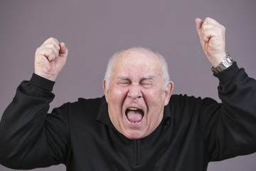 Photo of very emotional man screams on a gray background
