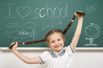 girl with pigtail drawing on school board