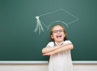 girl with academic cap drawing on school board