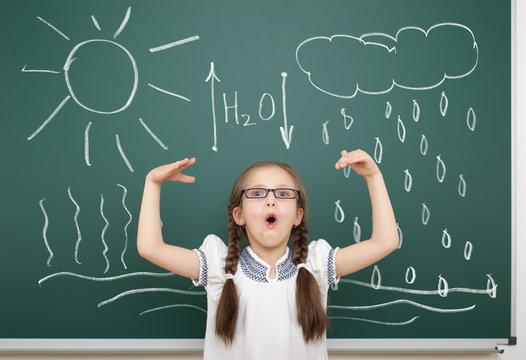 girl drawing water circulation on school board