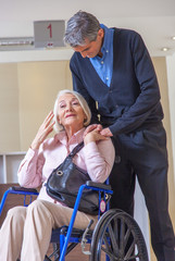 Woman on wheelchair with male assistant in hospital room