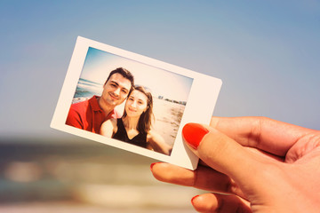 Retro Photo Of Girl Hand Holding Instant Photo Of Young Happy Couple On The Beach