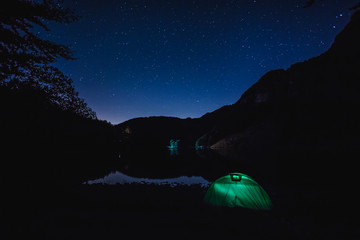 A tent lit, in a summer night under a starry sky is placed in a lake near the italian mountains