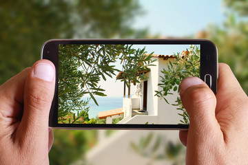 Male hand taking photo of Idyllic Greek house, villa, by the sea , between olive trees with cell, mobile phone. Greece holiday.