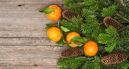 Mandarine fruits and christmas tree branches on wooden backgroun