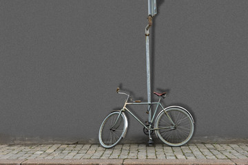 Old fashioned bicycle attached with lock to pole with road sign and gray wall in background