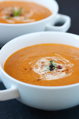 Vegetable soup with sun dried tomatoes and cream on a dark background