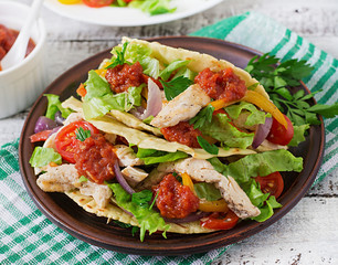 Mexican tacos with chicken, bell peppers, black beans and fresh vegetables and tomatoes sauce