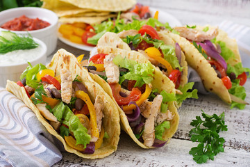 Mexican tacos with chicken, bell peppers, black beans and fresh vegetables.