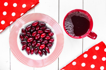 dogwood berries on white plate with red design and red cup of compote on white colored wooden table with red napkin at polka dots.top view