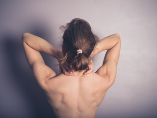 Naked young woman with neck pain