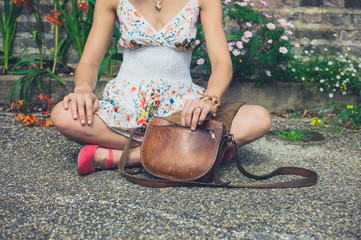 Woman sitting in street with her handbag