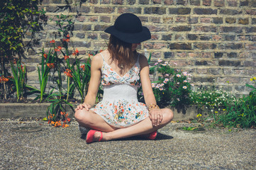 Young woman sitting by flowers outside