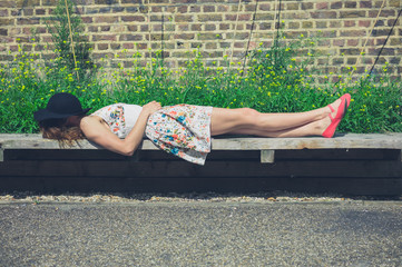 Young woman relaxing on bench outside