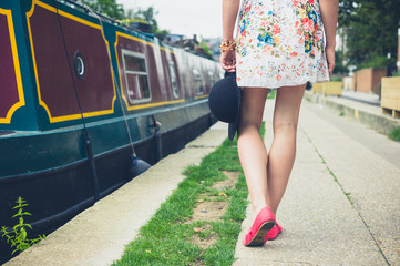 Young woman walking past houseboat on the canal