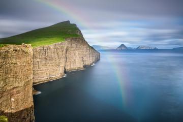 Wall Mural - Giant sea cliffs on Faroe Islands with a rainbow