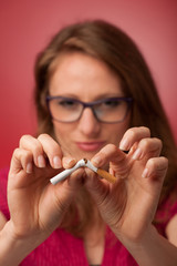 beautiful young woman breaks a cigarette as a gesture for quit s