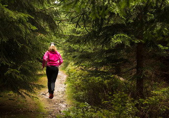 woman running on the forest trail in the rain