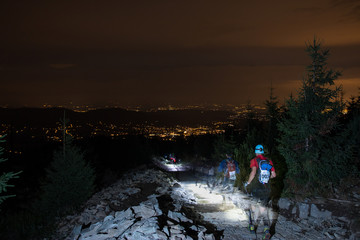 adventure night runners on the trail with head lamps and city lights