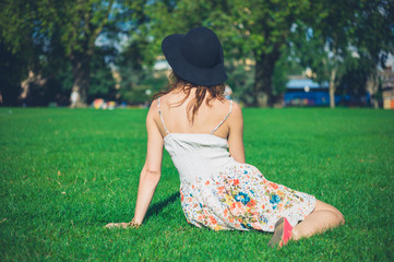 Young woman in hat sitting on grass in park