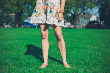 Woman in dress standing on grass in park