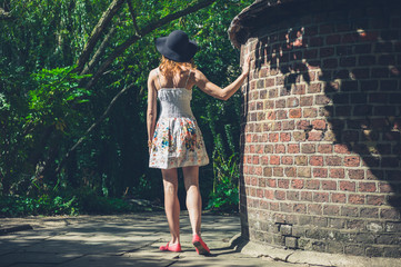 Young woman in dress and hat by brick wall